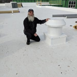 Martin Kolt on a flat rooftop with a Pop Vent Intake Vent with Curb Mount Flange